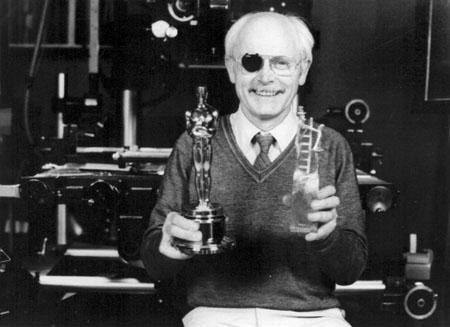 Frédéric Back présentant deux des multiples trophées qui ont couronné son film CRAC : l'Oscar remporté en 1982 et le trophée du Premier Prix au Fairytale Film festival à Odense au Danemark en 1981 Coll. Cinémathèque québécoise