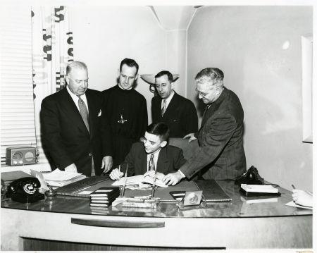 La signature du contrat : J.A. DeSève, le frère Grevais, Gérard Barbeau, son père, René Germain