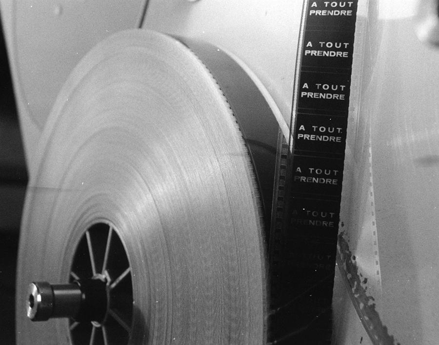 Photo d'une pellicule.[196?] Bobine de film et pellicule sur un appareil. Noir et blanc. 1995.0352.PH.34. Sur la pellicule est imprimé le titre «À tout prendre».